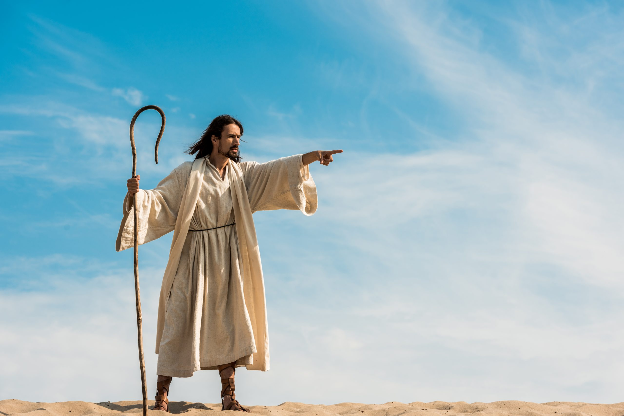bearded man holding wooden cane and pointing with finger in desert against sky